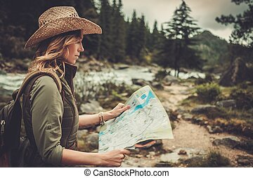 Woman hiker, searching right direction on map near wild...