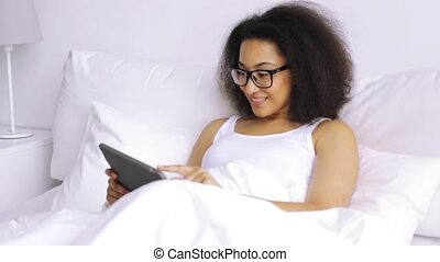african woman with tablet pc in bed at home