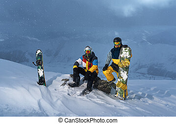 Two snowboarder snowy weather in mountains in the evening -...