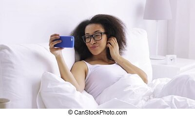 african woman with smartphone in bed at home - rest,...