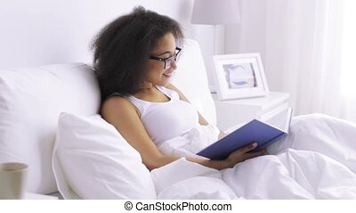 african woman reading book in bed at home bedroom - rest,...
