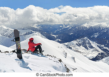 Snowboarder sitting on edge of the mountain - Snowboarder...
