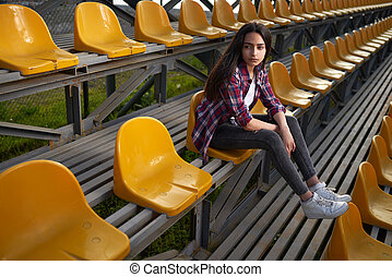 beautiful lonely woman sitting on tribunes and looks aside...