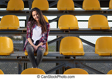 lonely cheerleader girl sitting in stands and smiles sweetly...