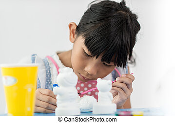 Asian child paints the colors of white plaster doll toys on...