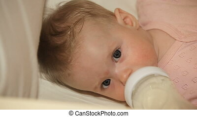 Baby drinking form bottle. - Beautiful, cute baby, lying in...