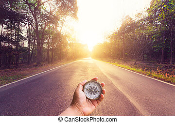 Hand holding compass on empty asphalt road and sunset