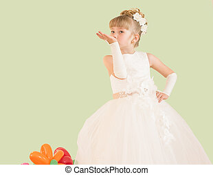 little girl in a ball gown isolated on a yellow background