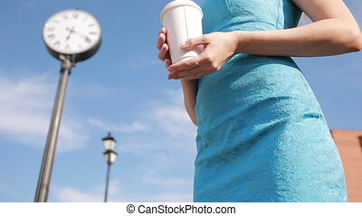 girl stands near the clock and drinking coffee. waiting