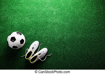 Soccer ball and cleats against green artificial turf, studio...