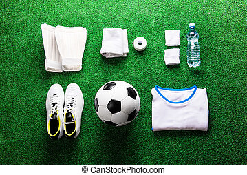 Soccer ball,cleats and various football stuff against...