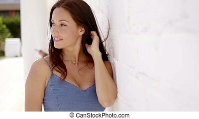 Attractive young brunette plays with her hair while pressing...