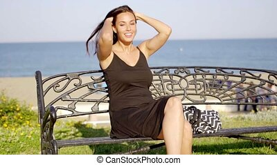 Smiling woman sitting waiting on a bench at the coast...