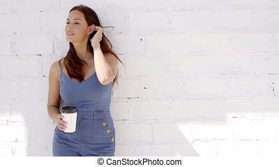 Young woman enjoying a cup of takeaway coffee - Young woman...