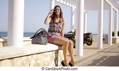Happy relaxed trendy young woman at the beach sitting on a...