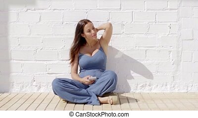 Happy young woman listening to music in the sun