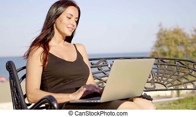 Attractive woman working outdoors on a laptop as she relaxes...