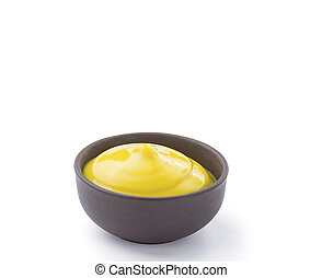 Mustard in brown bowl isolated on white background. Closeup.