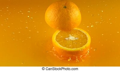 Orange hits orange juice surface and splits into halves....