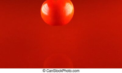 Whole ripe red tomato hits tomato juice surface and...