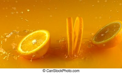 Cut ripe orange hits orange juice surface and rebounces....