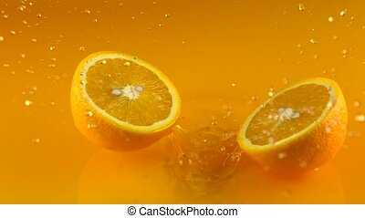 Orange falls on orange juice surface and splits into halves....