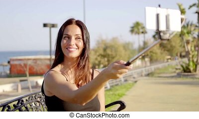 Smiling pretty young woman taking her selfie using a selfie...