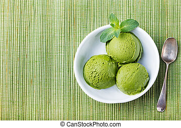 Green tea matcha ice cream scoop in white bowl on a wooden background Copy space Top view