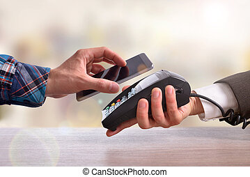 Customer paying a merchant with mobile phone front -...