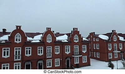 Snow against red brick townhouses super slow motion shot...