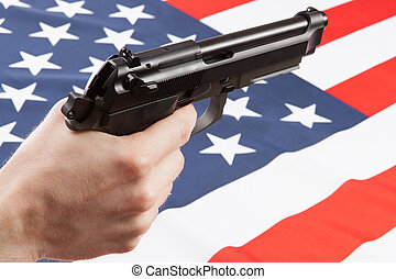 Gun in hand with ruffled national flag on background -...