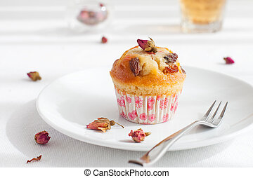 Muffin, mini cake, cup cake on a white plate with a rose...