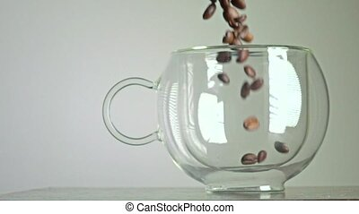 Roasted coffee beans being poured in a glass cup super slow...