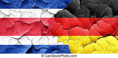 Costa Rica flag with Germany flag on a grunge cracked wall