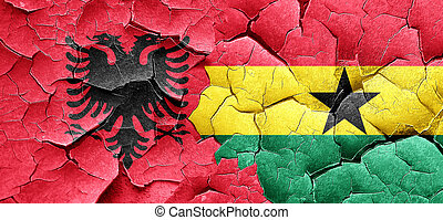 Albania flag with Ghana flag on a grunge cracked wall