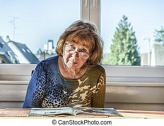 elderly attractive woman reading in a magazine - elderly...