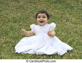 Hispanic Baby playing in the Grass - Portrait of a little...