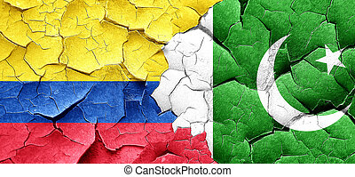 Colombia flag with Pakistan flag on a grunge cracked wall