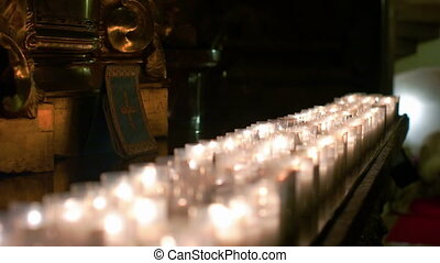 Candles Burning in a Row - Candles of praying people burning...
