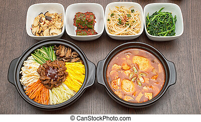 Korean bibimbap and kimchi soup with side dishes on wooden...