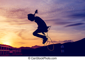 Girl  jumping rope in silhouette with sun set