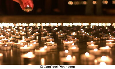 Woman Placing Her Candle in Between Other Candles - Adult...