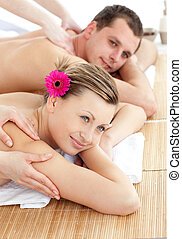 Smiling young couple receiving a back massage