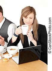 Serious businesswoman using a laptop while having breakfast...