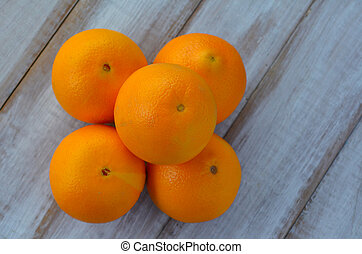 Five oranges on a wooden table Food background and texture...