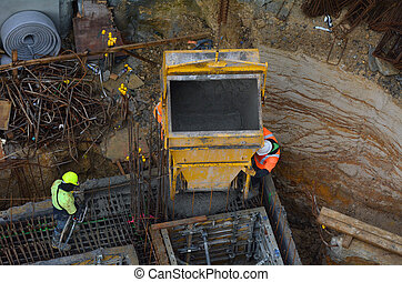 Construction site worker during concrete pouring into...