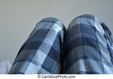 Legs of a man wearing pyjamas lie in bed. Laziness concept