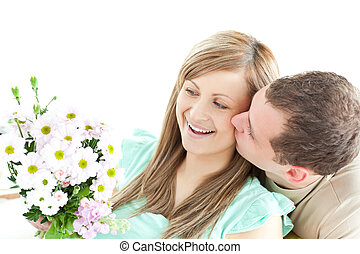 Enamored man giving a bouquet to his girlfriend against a...