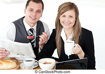 Young couple of business people reading a newspaper while...