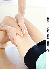 Close-up of a caucasian woman receiving a leg massage in a...